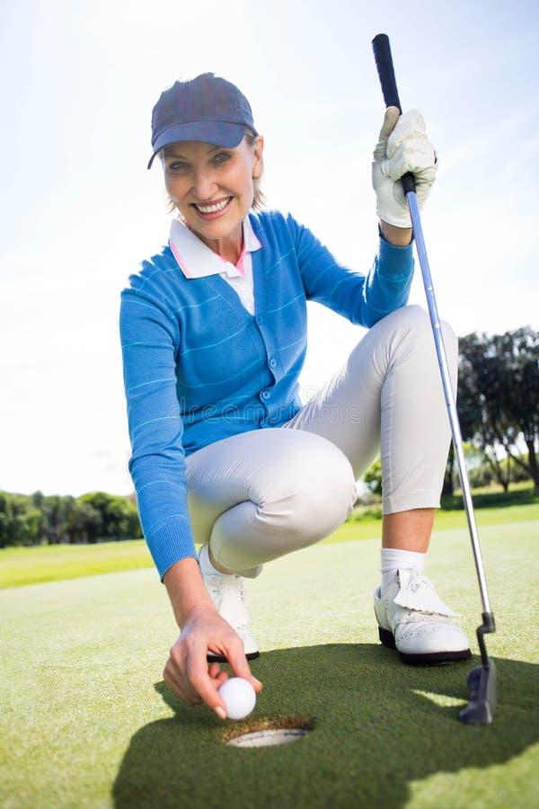 Uśmiechnięty dama golfisty klęczenie na kładzenie zieleni obraz royalty free