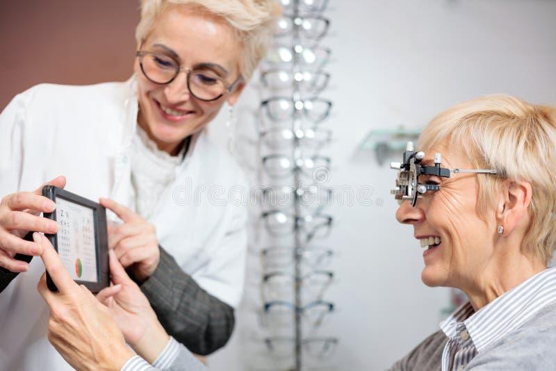 Uśmiechnięty dojrzały żeński oftalmolog egzamininuje starszej kobiety, trzyma oko mapę obraz royalty free