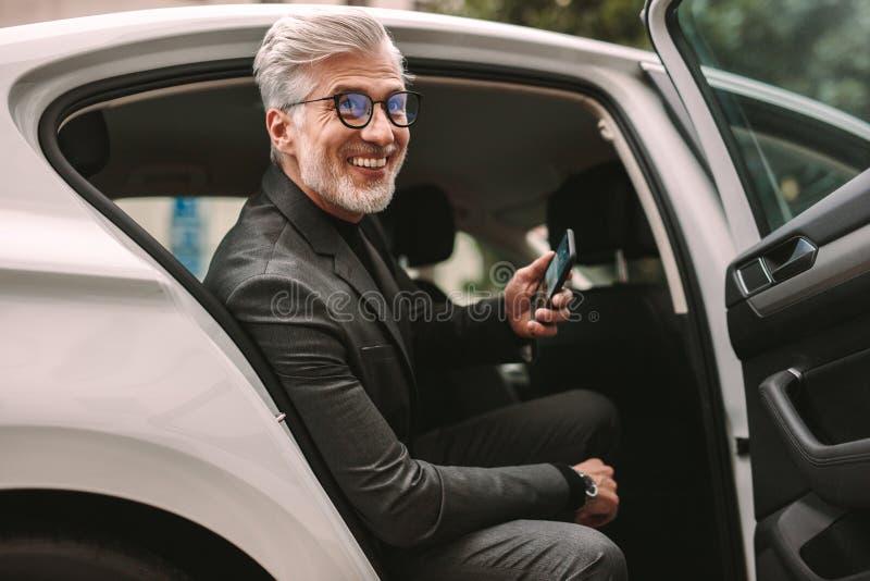 Uśmiechnięty dojrzały biznesmen w taxi obrazy royalty free