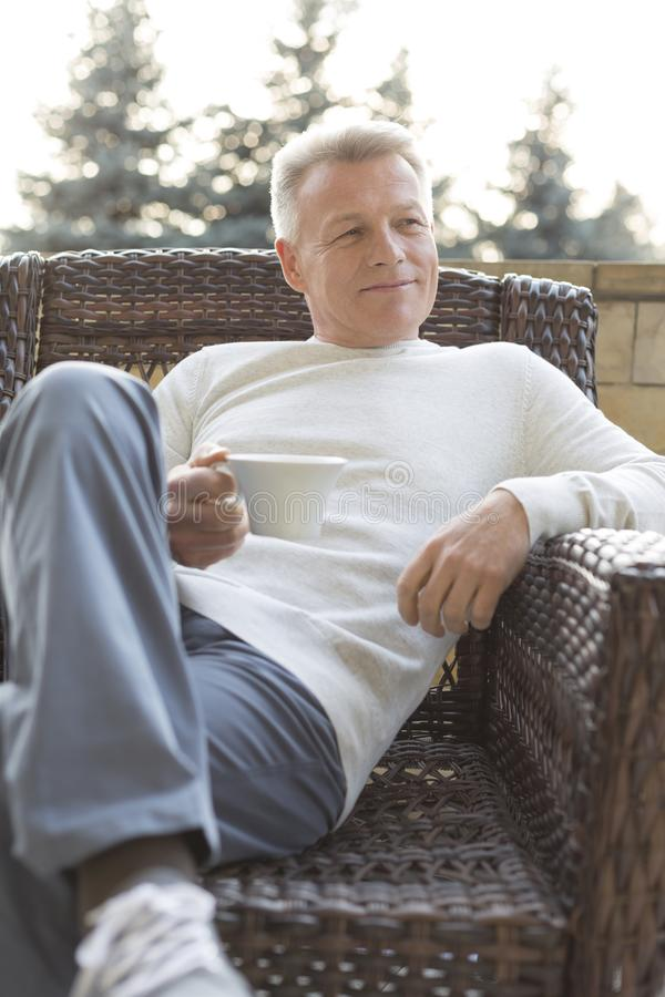 Uśmiechnięty dojrzały mężczyzny mienia napój podczas gdy siedzący na łozinowym krześle przy patiem fotografia stock