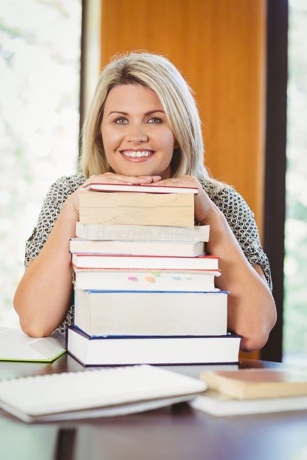 Uśmiechnięty dojrzały uczeń z stertą książki obraz royalty free