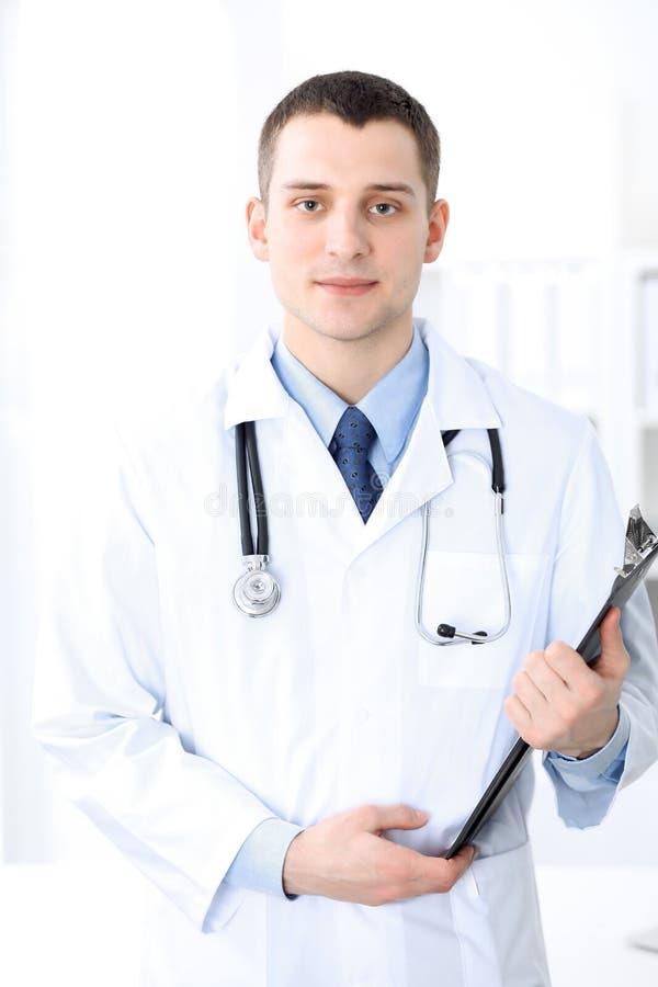 Uśmiechnięty doktorski czekanie dla jego drużyny podczas gdy stać pionowy obrazy stock