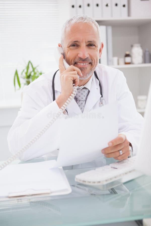 Uśmiechnięty doktorski telefonowanie i używać komputer fotografia royalty free