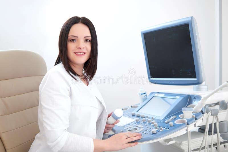 Uśmiechnięty doktorski używa ultradźwięku wyposażenie, komputer i obraz stock