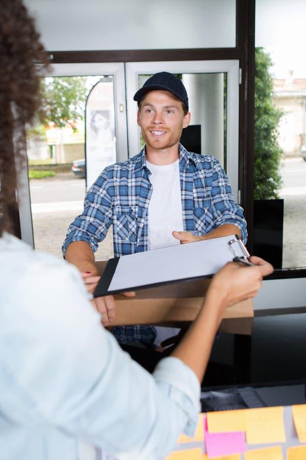 Uśmiechnięty doręczeniowego mężczyzna i młodej kobiety podpisywania schowek zdjęcia stock