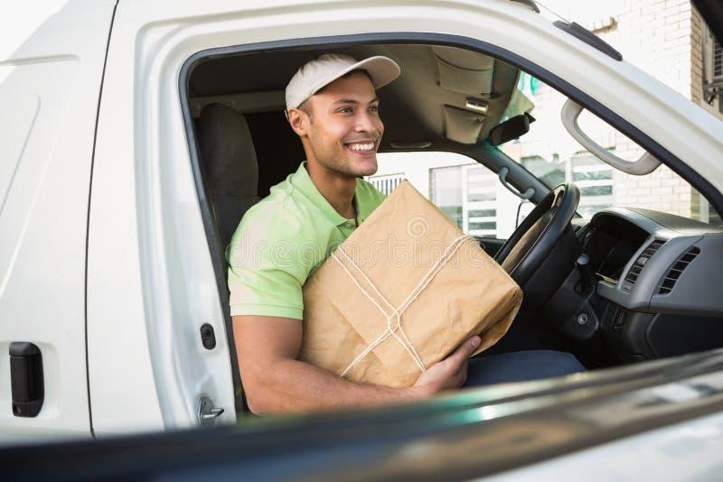 Uśmiechnięty doręczeniowy kierowca w jego Samochodu dostawczego Mienie pakuneczku fotografia royalty free