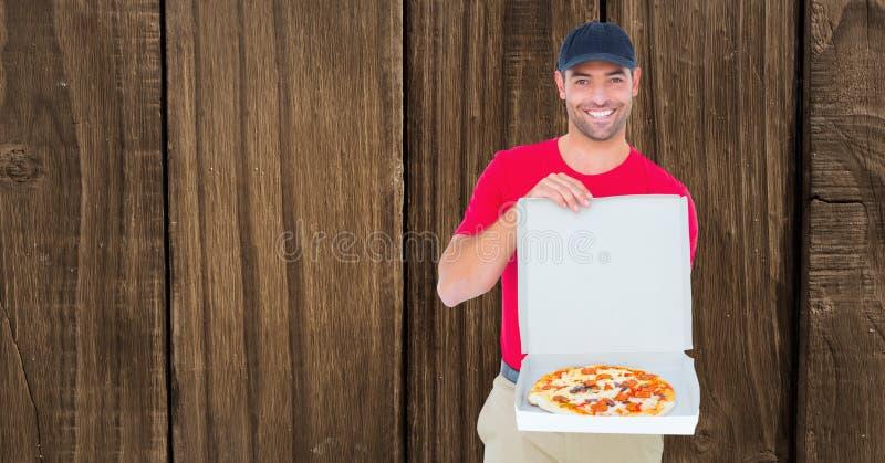 Uśmiechnięty doręczeniowy mężczyzna pokazuje pizzę przeciw drewnianej ścianie obraz royalty free
