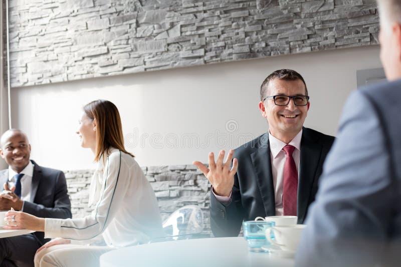 Uśmiechnięty dorośleć mężczyzna opowiada z męskim kolegą w biurowym bufecie obrazy royalty free