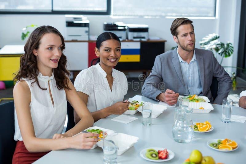 Uśmiechnięty dyrektor wykonawczy ma posiłek w biurze fotografia royalty free