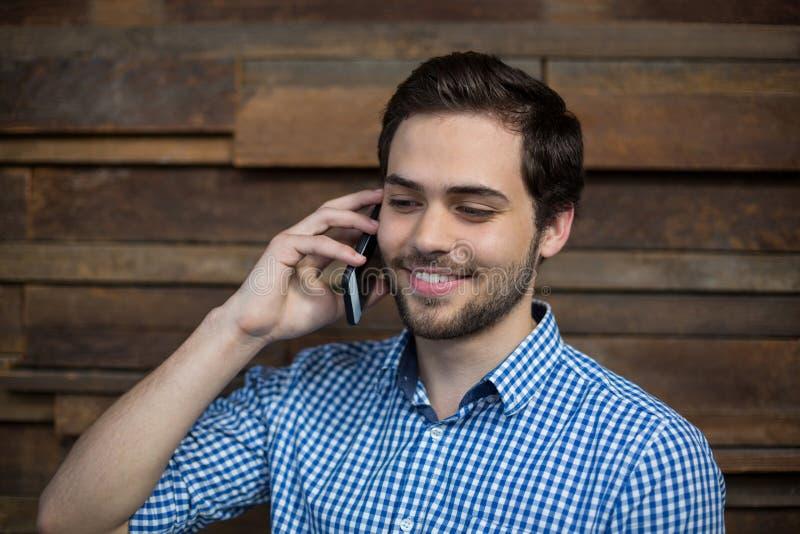 Uśmiechnięty dyrektor wykonawczy opowiada na telefonie komórkowym fotografia stock