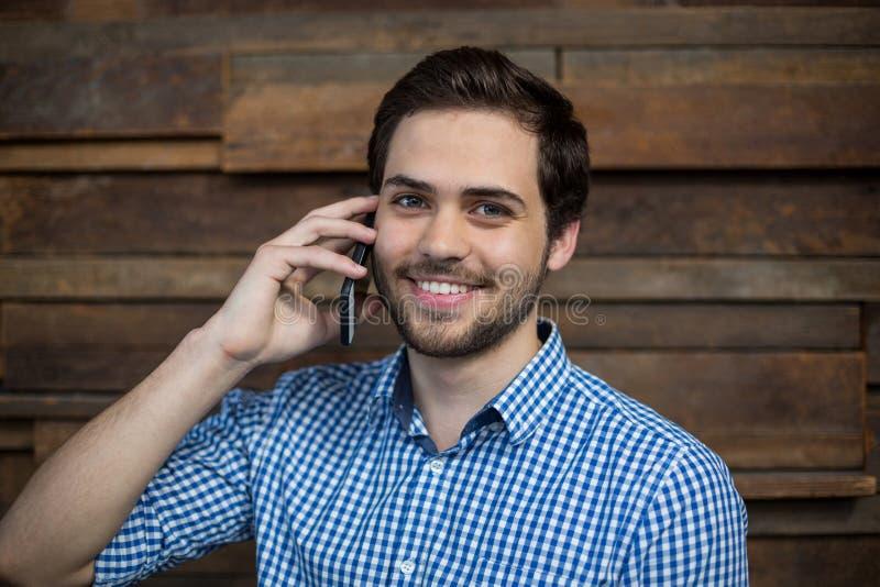 Uśmiechnięty dyrektor wykonawczy opowiada na telefonie komórkowym w biurze fotografia stock