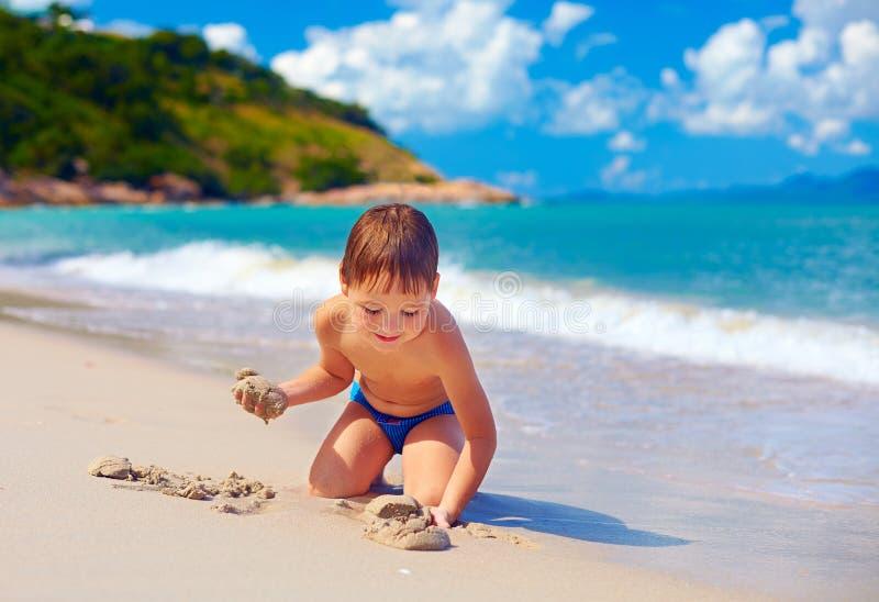 Uśmiechnięty dzieciak bawić się w piasku na tropikalnej wyspy plaży obrazy stock