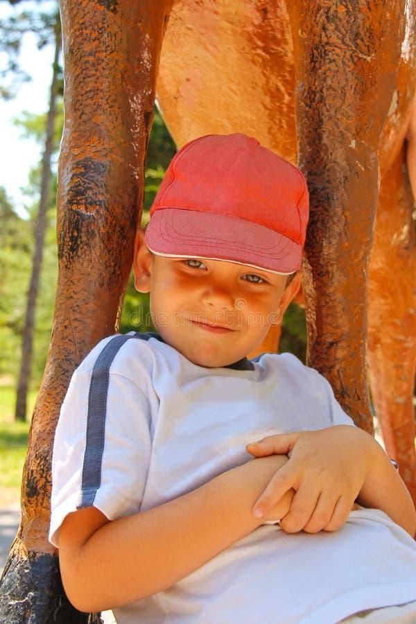 Uśmiechnięty dzieciak jest ubranym nakrętkę w parku zdjęcia royalty free