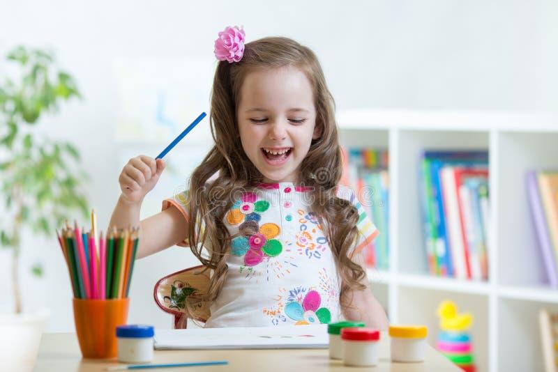Uśmiechnięty dzieciaka rysunek z kolorów ołówkami w opieki dziennej centrum zdjęcia royalty free