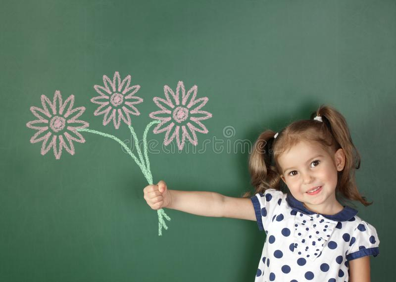 Uśmiechnięty dziecko dziewczyny chwyt rysujący kwitnie blisko szkolnego blackboard zdjęcia royalty free