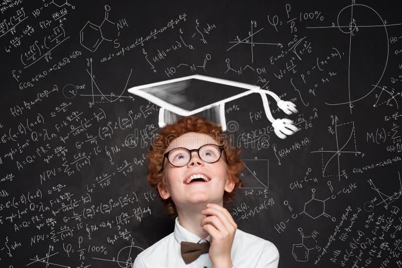 Uśmiechnięty dziecko uczeń na blackboard z nauki i matematyk formułą zdjęcie stock