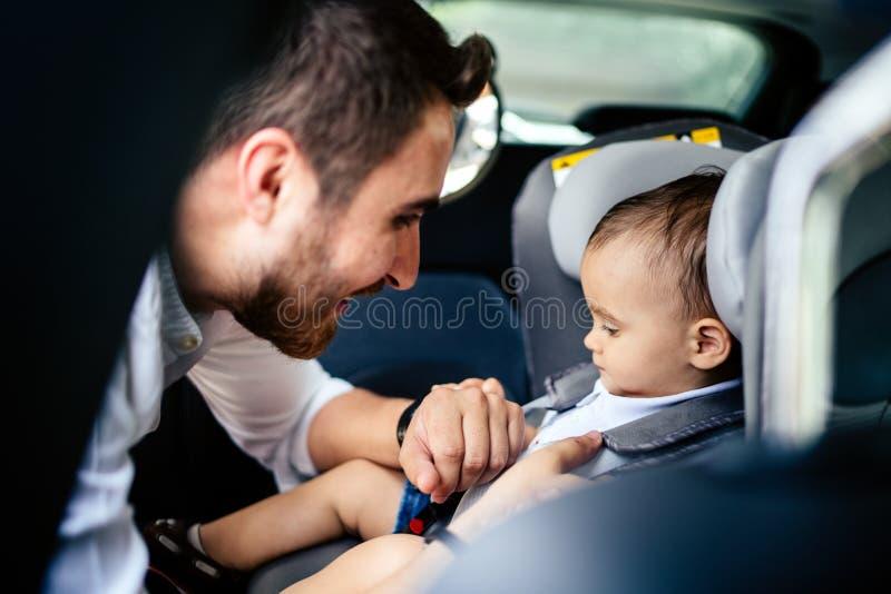 Uśmiechnięty dziecko w dziecka samochodowym siedzeniu iść dla rodzinnego roadtrip Ojciec przymocowywa Zbawczego seatbelt obrazy stock