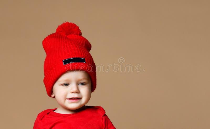 Uśmiechnięty dziecko w trykotowym kapeluszowym obsiadaniu na białym tle obrazy royalty free
