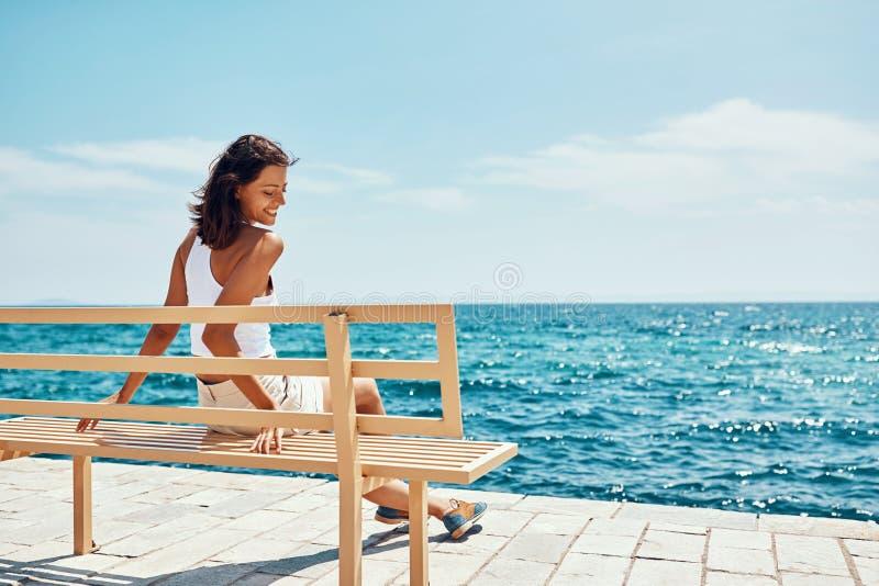 Uśmiechnięty dziewczyna podróżnika obsiadanie na ławce blisko plażowego przyglądającego morza zdjęcie stock
