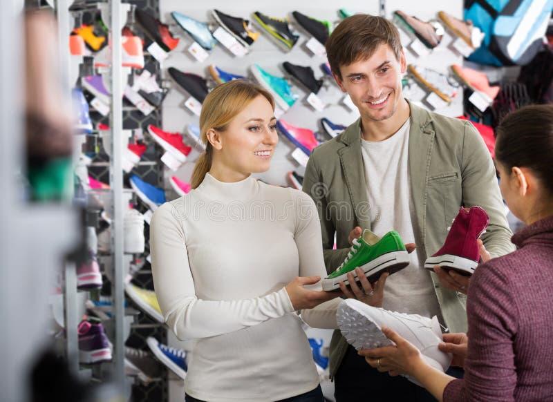 Uśmiechnięty dziewczyna sprzedawca pomaga klienta w butach wydziałowych zdjęcie stock