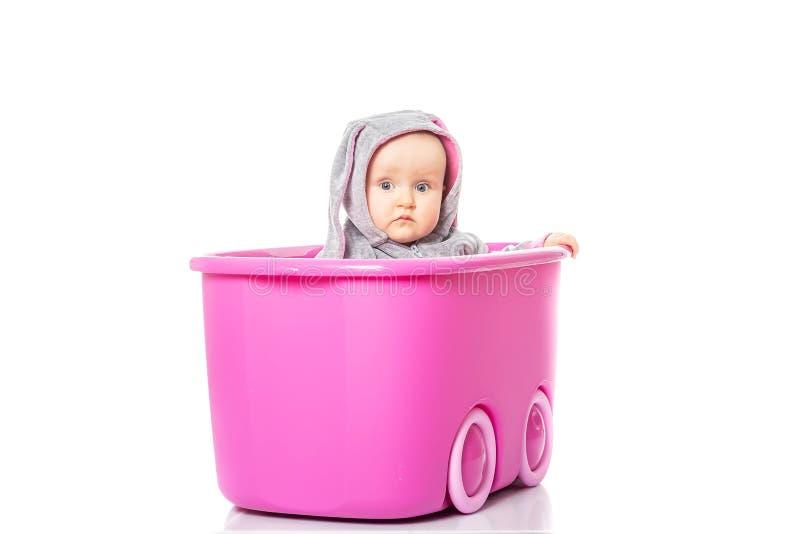 Uśmiechnięty dziewczynki obsiadanie wśrodku różowego pudełka na białym tle dziecka ` s gry obraz royalty free