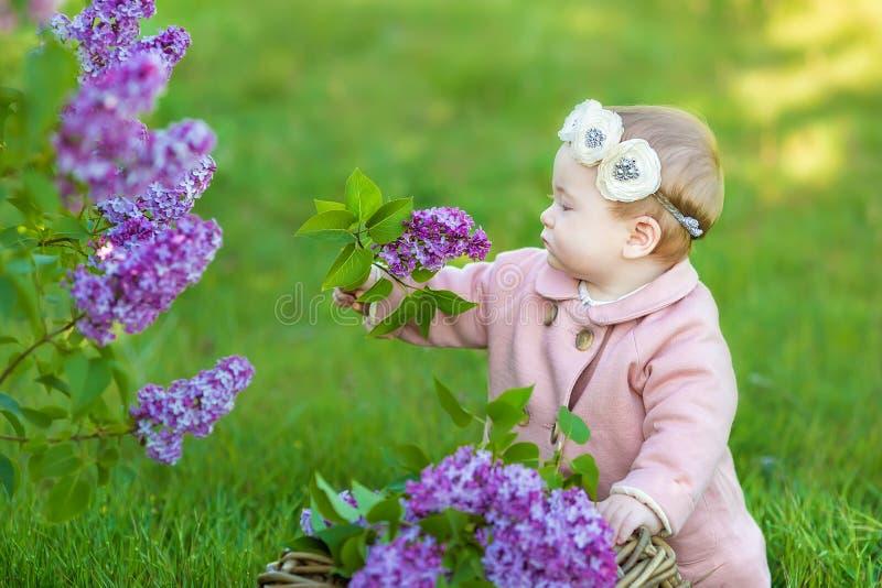 Uśmiechnięty dziewczynki 1-2 roczniak jest ubranym kwiatu wianek, trzyma bukiet bez outdoors patrzeć kamerę lato wiosny czas obraz royalty free