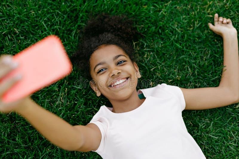 Uśmiechnięty dziewczyny lying on the beach na brać selfie i trawie fotografia royalty free
