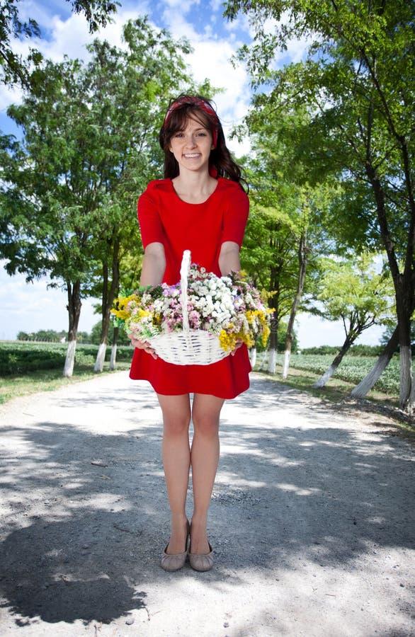 Uśmiechnięty dziewczyny mienia kosz z kwiatami zdjęcie royalty free