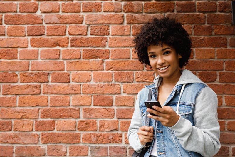 Uśmiechnięty dziewczyny mienia telefon komórkowy zdjęcie stock