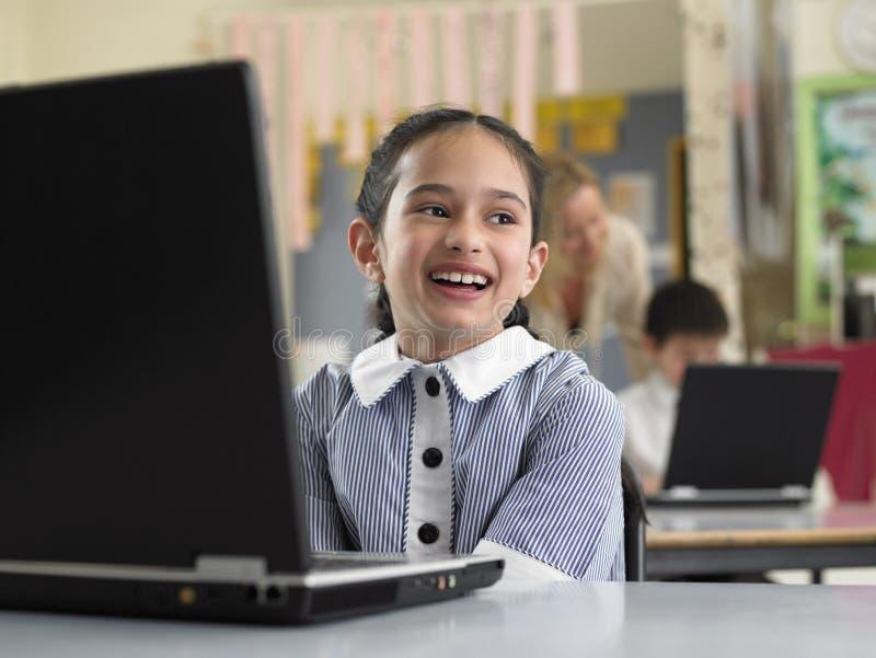 Uśmiechnięty dziewczyny obsiadanie laptopem W sala lekcyjnej zdjęcia stock