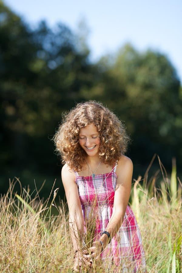 Uśmiechnięty dziewczyny odprowadzenie przez wysokiej trawy obraz royalty free