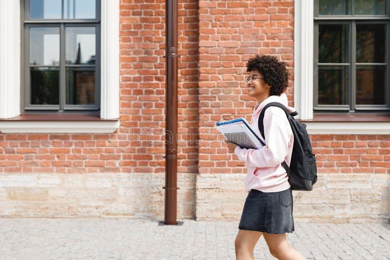 Uśmiechnięty dziewczyny odprowadzenie z książkami zdjęcie royalty free