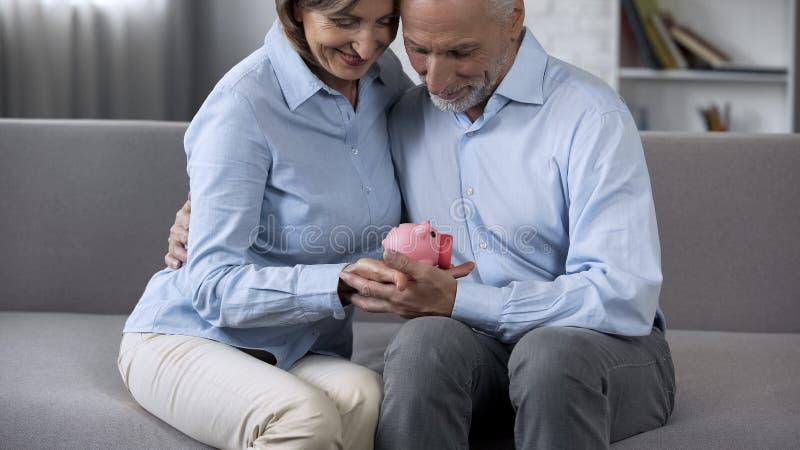Uśmiechnięty emeryt pary obsiadanie na leżanki mienia prosiątka banku, kredytowanie usługa fotografia stock