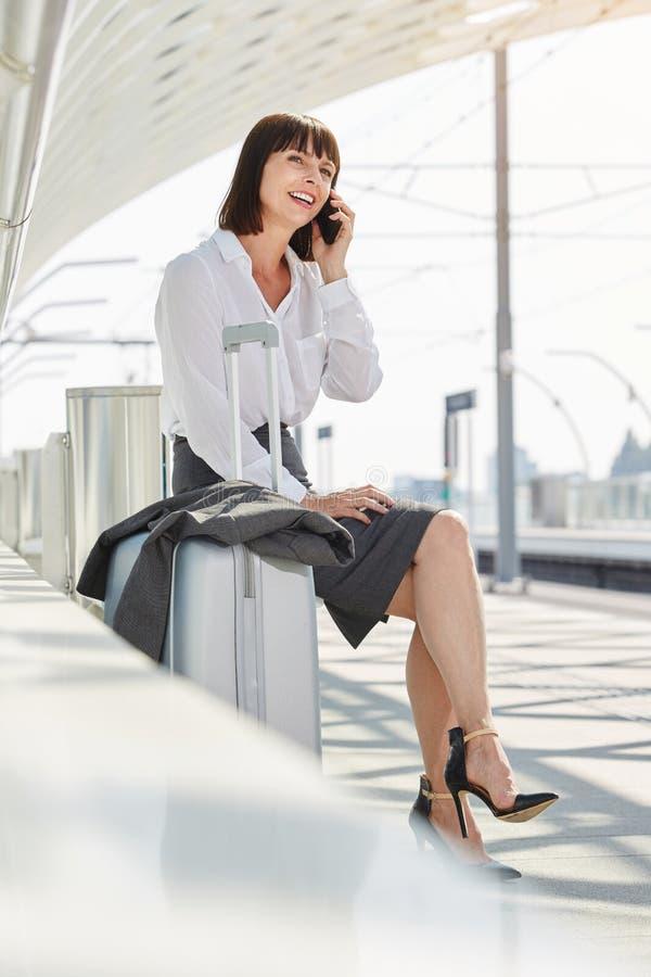 Uśmiechnięty fachowej kobiety czekanie przy platformą opowiada na telefonie obrazy stock