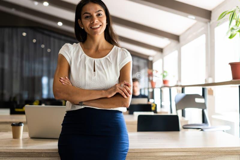 Uśmiechnięty fachowy bizneswoman w przypadkowym, z rękami krzyżował pozycję w biurze obraz royalty free