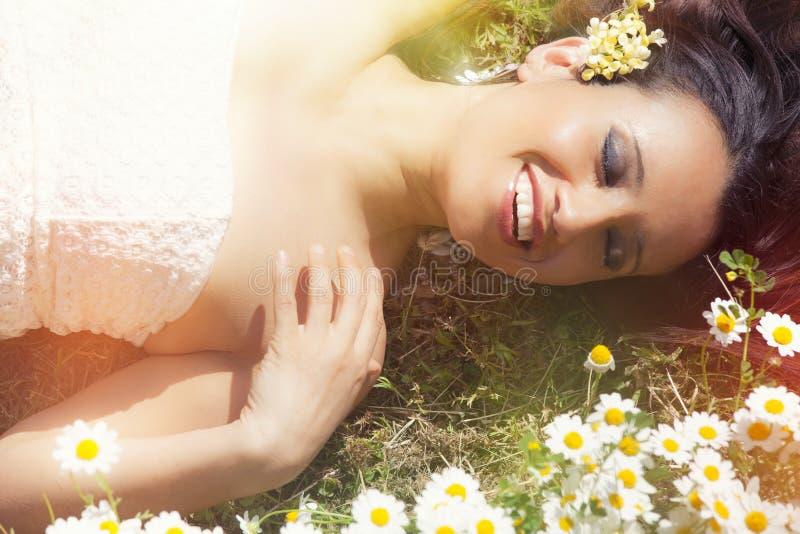 Uśmiechnięty harmonii kobiety lying on the beach na trawie z stokrotkami Zaświeca podnośniki zdjęcia stock