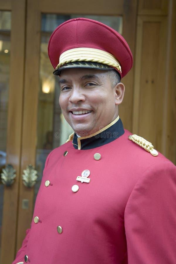 Uśmiechnięty hotelowy bellman z czerwoną kurtką na w Rzym, Włochy, Europa zdjęcia stock