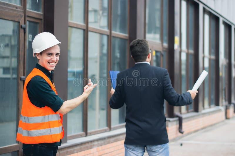 Uśmiechnięty i ostry inżynier pokazuje sprośnego środkowego palec zdjęcie stock
