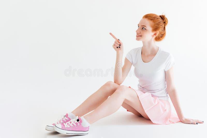 Uśmiechnięty imbirowy dziewczyny obsiadanie na podłoga i wskazywać daleko od obraz stock