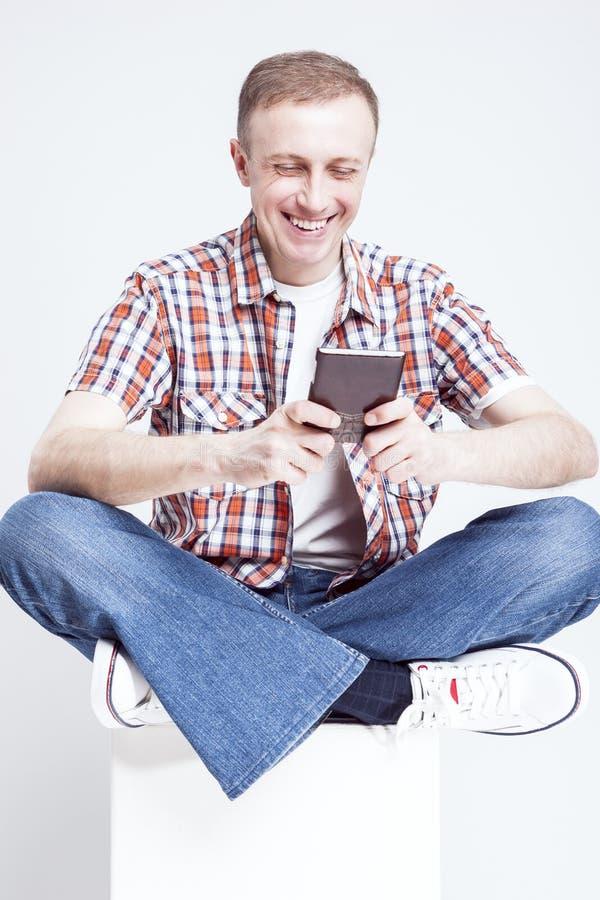 Uśmiechnięty Kaukaski mężczyzna Gawędzi na telefonie komórkowym w W kratkę koszula i cajgach zdjęcia royalty free