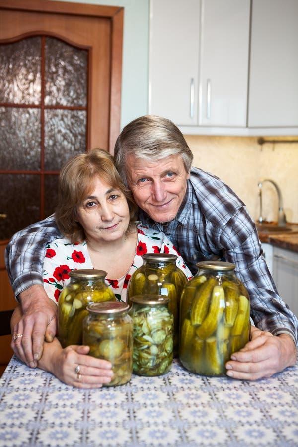 Uśmiechnięty Kaukaski starzejący się pary obsiadanie w domowej kuchni z szklanymi puszkami z pickler zdjęcie stock