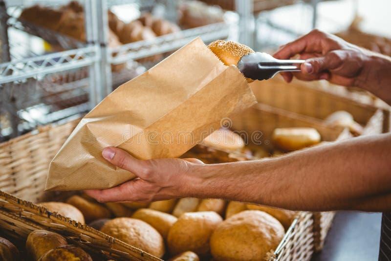 Uśmiechnięty kelner bierze chleb z tongs obrazy stock