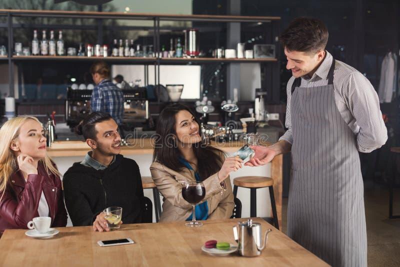 Uśmiechnięty kelner bierze zapłatę od klienta zdjęcia stock
