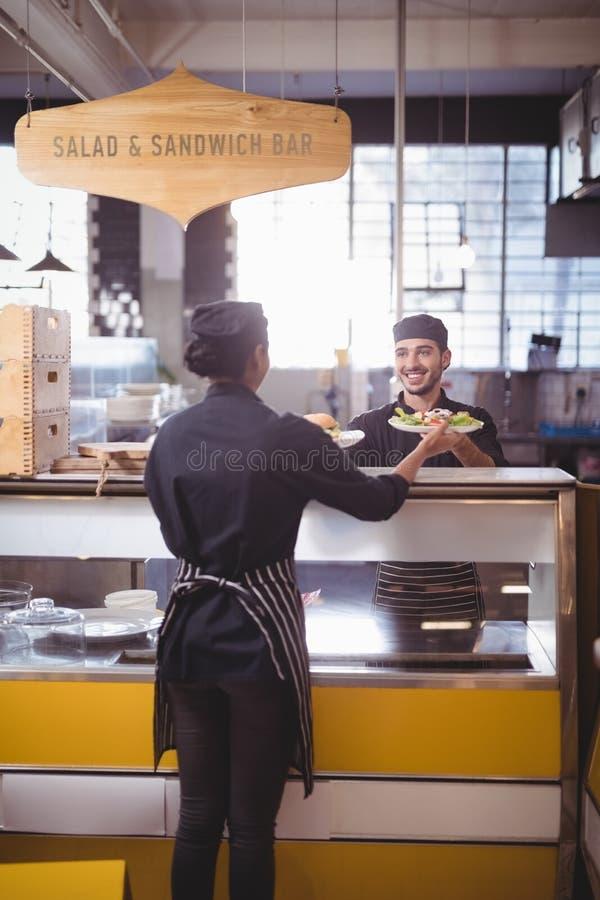 Uśmiechnięty kelner daje jedzenie talerze kelnerka przy kontuarem fotografia royalty free