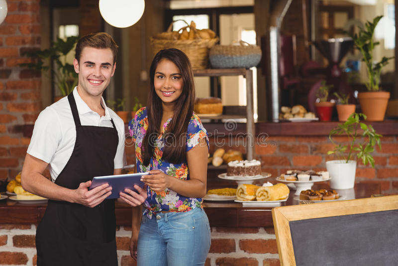 Uśmiechnięty kelner i ładny klient patrzeje na pastylce zdjęcia stock