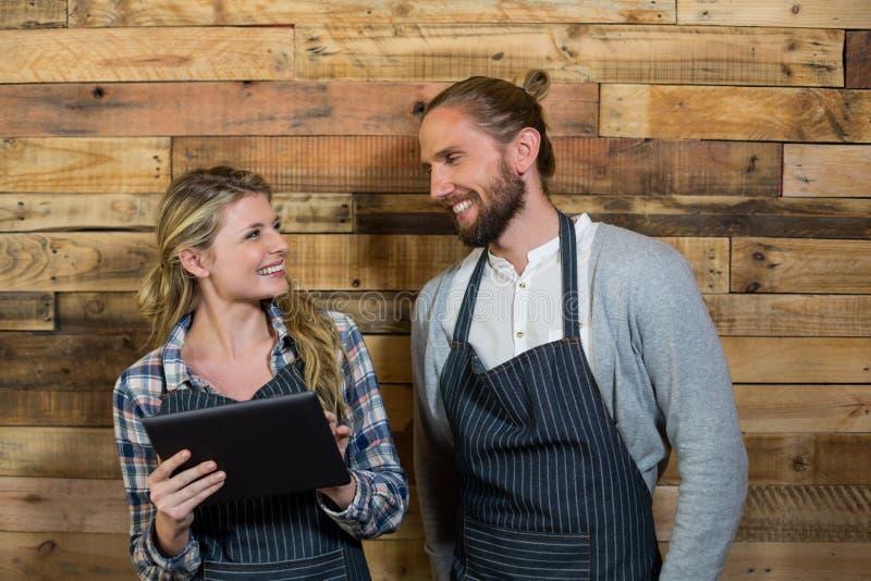 Uśmiechnięty kelner i kelnerka używa cyfrową pastylkę przeciw drewnianej ścianie zdjęcie stock