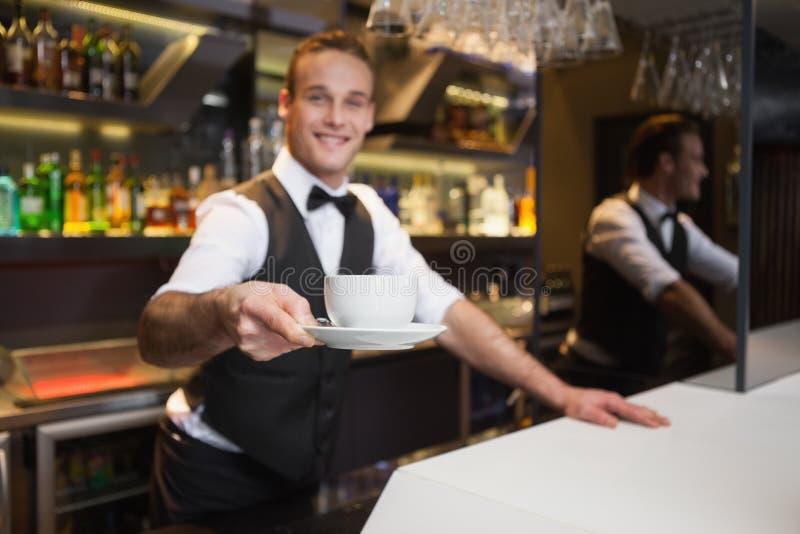 Uśmiechnięty kelner oferuje filiżankę kawy ono uśmiecha się przy kamerą obraz stock