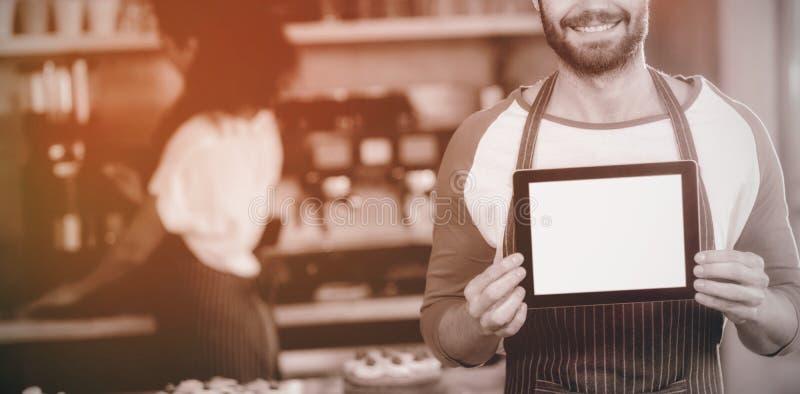 Uśmiechnięty kelner pokazuje cyfrową pastylkę przy kontuarem w café obraz stock