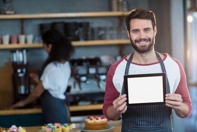 Uśmiechnięty kelner pokazuje cyfrową pastylkę przy kontuarem w café zdjęcie stock