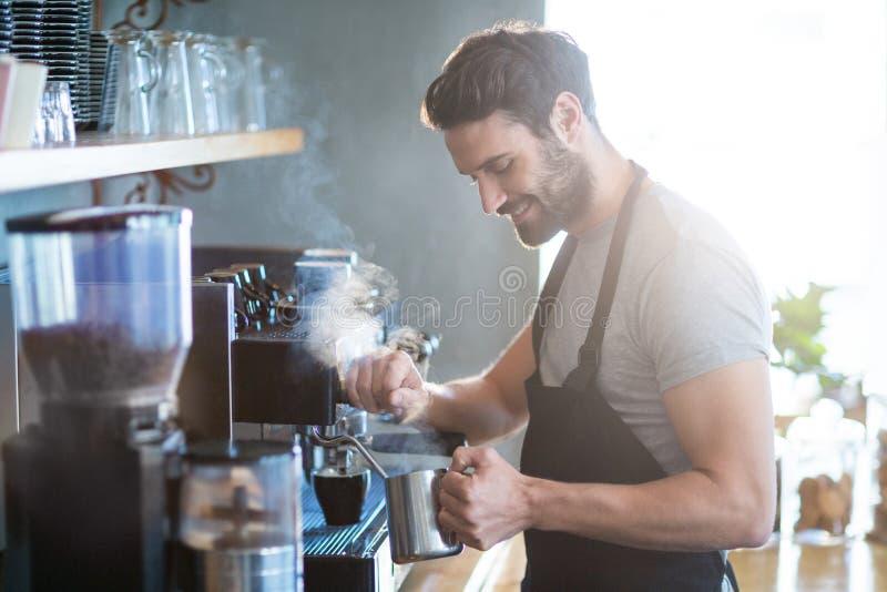 Uśmiechnięty kelner robi filiżance kawy zdjęcia stock